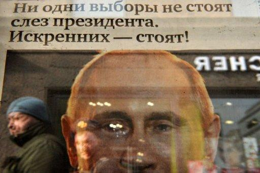 A woman is reflected in glass covering a copy of news paper featuring crying Vladimir Putin in Moscow