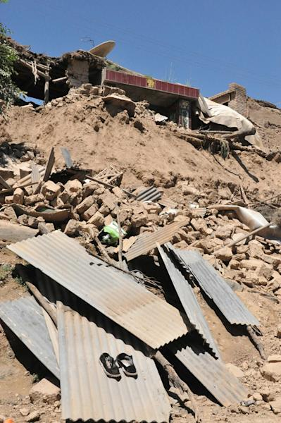 In this July 22, 2013 photo released by Xinhua News Agency, a damaged house stands in rubble following an earthquake that hit Majiagou Village of Minxian County, northwest China's Gansu Province. A strong earthquake struck near the surface in a dry, hilly farming area in western China early Monday, killing at least 54 people, injuring nearly 300, and shattering thousands of homes, the local government said. (AP Photo/Xinhua, Tu Guoxi) NO SALES