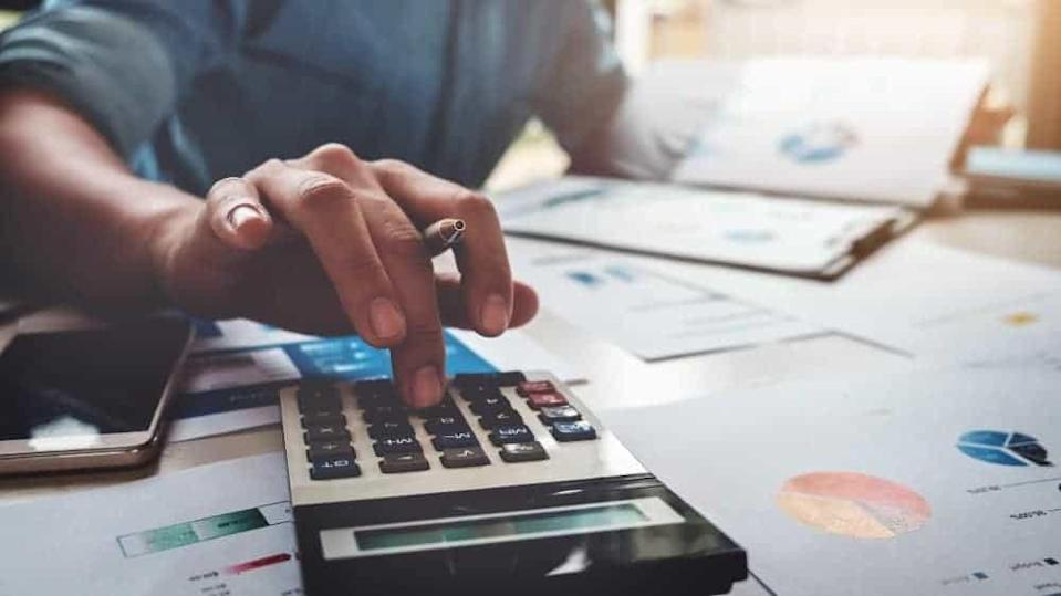 Business accounting concept, Business man using calculator with computer laptop, budget and loan paper in office.