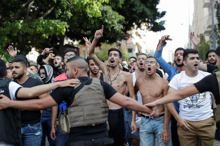 The Lebanese army forms a human-chain to block supporters of the Lebanese Shiite movements Hezbollah and Amal as they shout slogans against protesters in central Beirut on Saturday