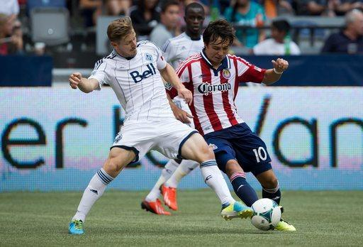 Vancouver Whitecaps' Jordan Harvey, left, defends against Chivas USA's Erick Torres, of Mexico, during the second half of an MLS soccer game, Sunday, Sept. 1, 2013 in Vancouver, British Columbia. (AP Photo/The Canadian Press, Darryl Dick)