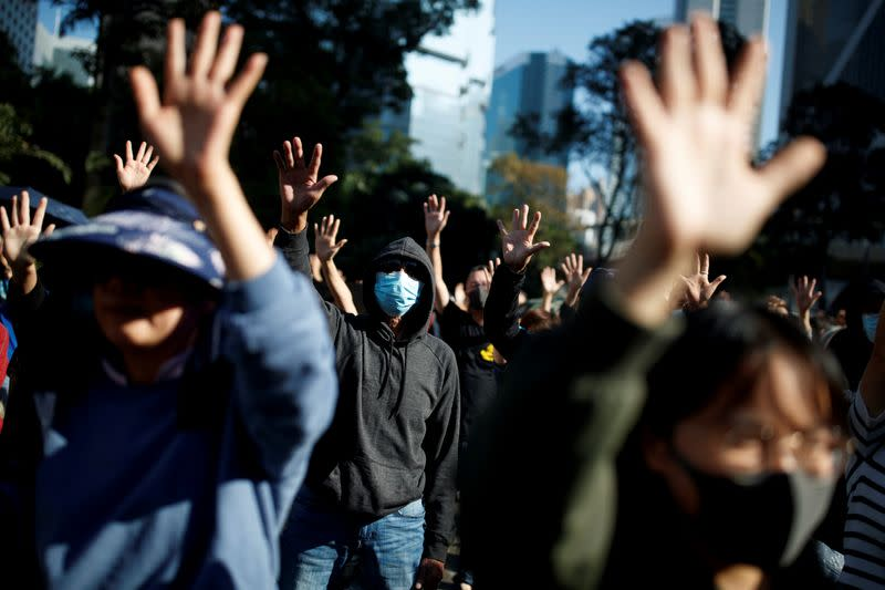 """FILE PHOTO: People raise their hands as they sing the protest anthem """"Glory to Hong Kong"""" during an anti-government protest in the Central district of Hong Kong"""