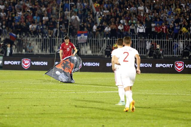 Serbia's Stefan Mitrovic, left, catches a flag with Albanian symbols suspended over the Partizan stadium from a drone during the Euro 2016 Group I qualifying match between Serbia and Albania in Belgrade, Serbia, Tuesday, Oct. 14, 2014. The European Championship qualifier between Serbia and Albania was suspended on Tuesday after pitch skirmishes involving players and fans over an Albanian flag symbol with the legend autochthonous, that was flown above the stadium by a drone. The match score was 0-0 at the time. (AP Photo/Marko Drobnjakovic)