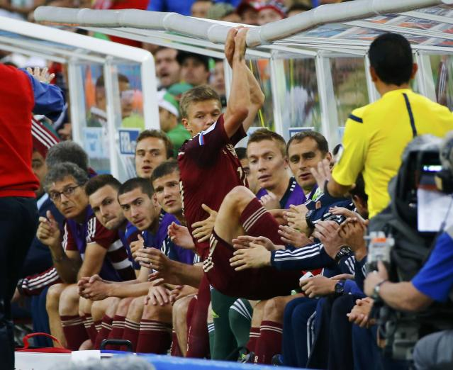 Russia's Oleg Shatov crashes into the team's bench during their 2014 World Cup Group H soccer match against Algeria at the Baixada arena in Curitiba June 26, 2014. REUTERS/Murad Sezer (BRAZIL - Tags: SOCCER SPORT WORLD CUP TPX IMAGES OF THE DAY)
