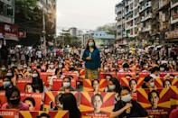 Anti-coup protesters with images of detained leader Aung San Suu Kyi sit along a street in Yangon