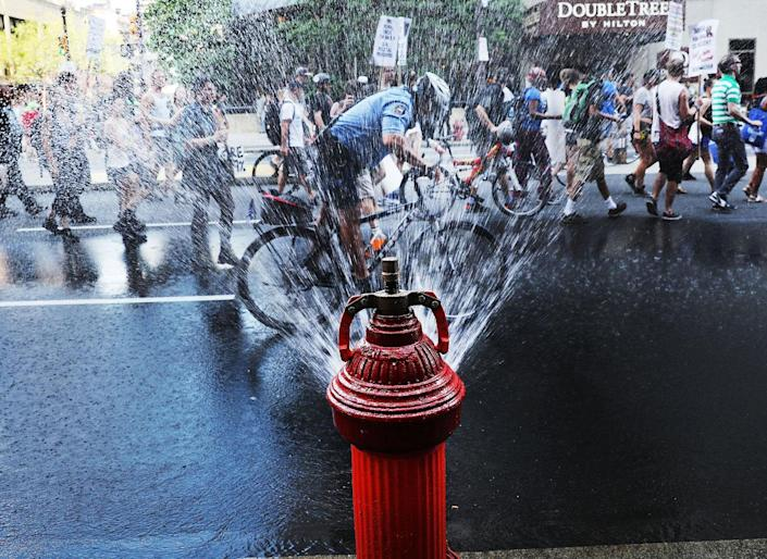 <p>A police officer cools off by riding through an open fire hydrant on a hot afternoon during a Black Lives Matter protest in downtown Philadelphia during the Democratic National Convention on July 26, 2016 in Philadelphia, Pa. (Photo: Spencer Platt/Getty Images)</p>