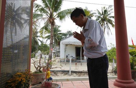 Colonel Vo Cao Tri prays at a monument with a list of names of victims who were killed by US soldiers in the My Lai massacre on March 16, 1968, in his village of My Lai, Vietnam March 14, 2016. REUTERS/Kham