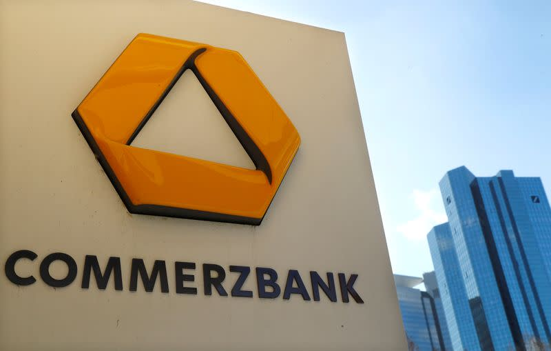 A sign for an ATM of Commerzbank is seen next to the headquarters of Deutsche Bank (R) in Frankfurt