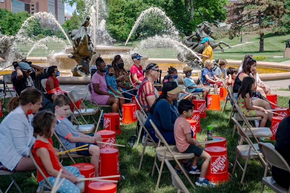 As part of Make Music Kansas City, participants tap on buckets during the Urban Bucket Brigade Workshop at Mill Creek Park, Monday, June 21, 2021 in Kansas City. Jaisson Taylor led the workshop teaching rhythms to the group as Kansas City made its' debut on Make Music Day, a world-wide celebration of music happening in over 1,000 cities in 120 countries. Over 70 free musical events were held city-wide as part of the event.