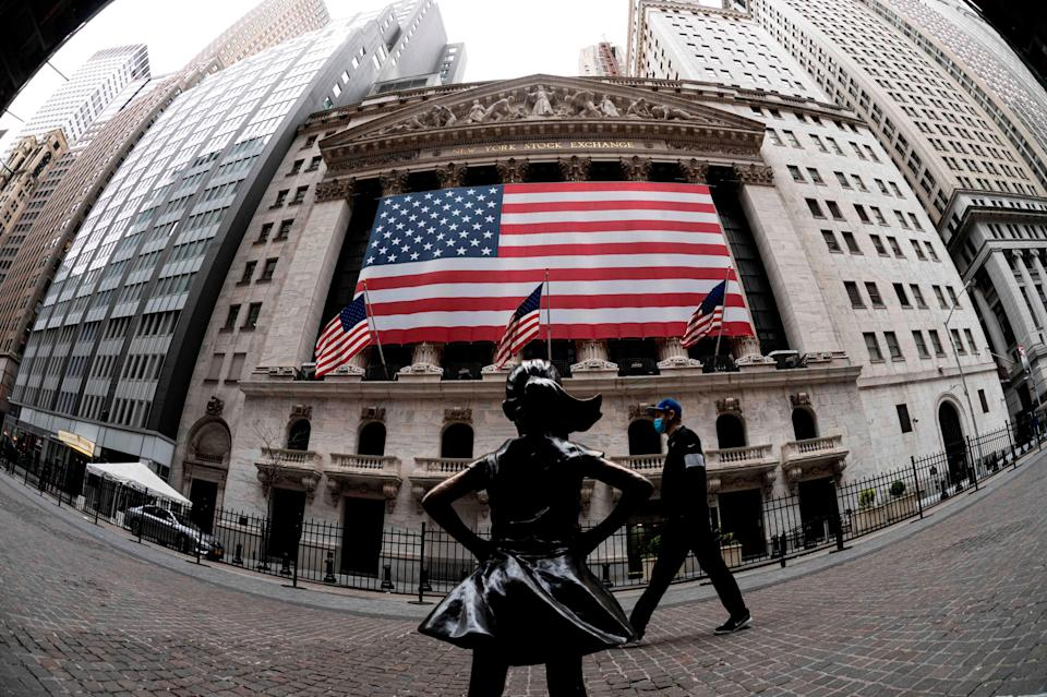 The fearless girl statue and the New York Stock Exchange (NYSE) are pictured on April 20, 2020 at Wall Street in New York City. - Wall Street opened lower on Monday as traders grappled with a drop in oil prices to 22-year lows as the coronavirus pandemic sapped demand for energy.