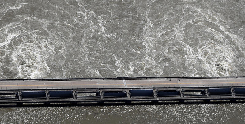 In this Wednesday, May 29, 2019 photo, two cyclists ride along the Old River Control Structure, as swelling waters from the Mississippi River are diverted through the U.S. Army Corps of Engineers structure into the Atchafalaya Basin, in Vidalia, La. (AP Photo/Gerald Herbert)
