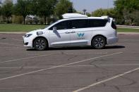 A Waymo minivan arrives to pick up passengers for an autonomous vehicle ride, Wednesday, April 7, 2021, in Mesa, Ariz. Waymo, a unit of Google parent Alphabet Inc., is one of several companies testing driverless vehicles in the U.S. But it's the first offering lifts to the public with no humans at the wheel who can take over in sticky situations.(AP Photo/Ross D. Franklin)