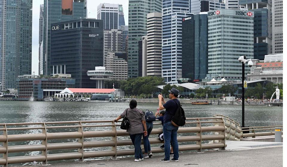 People take pictures of Marina Bay in Singapore, as the country's fake news law is challenged in court. Photo: AFP