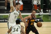 Atlanta Hawks' Trae Young loks to get past Milwaukee Bucks' Brook Lopez and Giannis Antetokounmpo during the second half of Game 2 of the NBA Eastern Conference basketball finals game Friday, June 25, 2021, in Milwaukee. (AP Photo/Morry Gash)