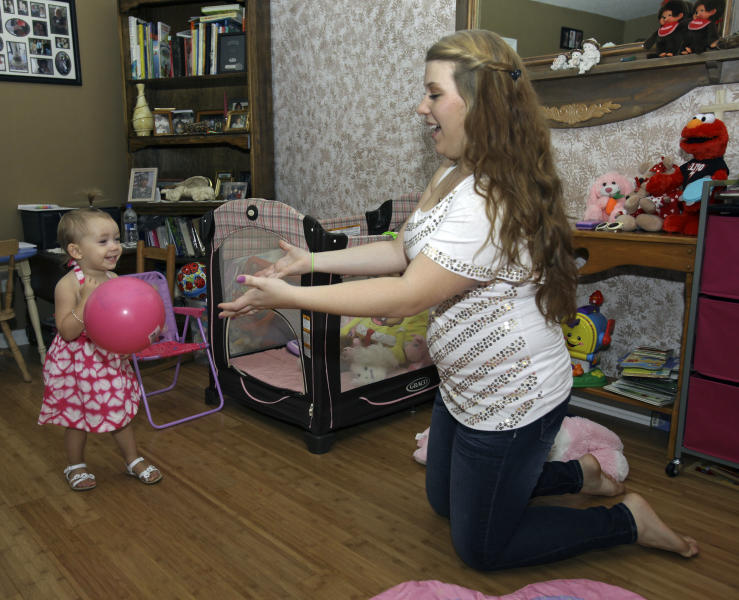 In this Monday, Sept. 10, 2012 photo, Kali Gonzalez, right, plays with her daughter Kiah, 2, at their home in St. Augustine, Fla. A new report by the National Women's Law Center says offering pregnant teens extra support would ultimately save taxpayers money by helping them become financially independent and not dependent on welfare. (AP Photo/John Raoux)