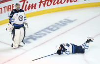 Winnipeg Jets' Josh Morrissey lays on the ice as Winnipeg Jets goaltender Connor Hellebuyck looks up at the replay following a short-handed goal by Montreal Canadiens' Joel Armia, not shown, during the second period of an NHL Stanley Cup playoff hockey game in Montreal, Sunday, June 6, 2021. (Paul Chiasson/The Canadian Press via AP)