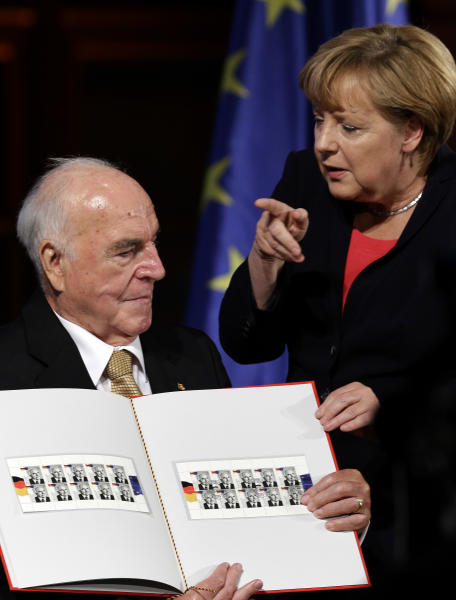 German Chancellor Angela Merkel points as she hands over a stamp to former German Chancellor Helmut Kohl showing himself during a reception of the Konrad-Adenauer Foundation in Berlin, Germany, Thursday, Sept. 27, 2012. The Konrad-Adenauer-Foundation will celebrate the 30th anniversary of the start of Kohl's chancellorship on Oct. 1, 1982. (AP Photo/Michael Sohn)