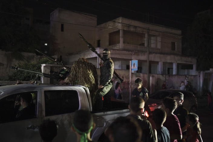 Hamas militants ride on a pickup truck during a rally in Gaza City, Wednesday, June 9, 2021. Hamas militants held a rally to commemorate the members of the group who were killed in an 11-day war with Israel in May. (AP Photo/Felipe Dana)