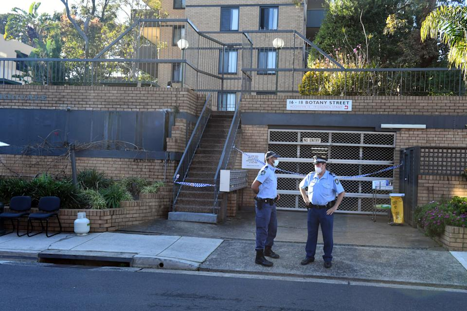 Two NSW police officers stand outside the Bondi Junction building where nine people have tested positive for Covid.