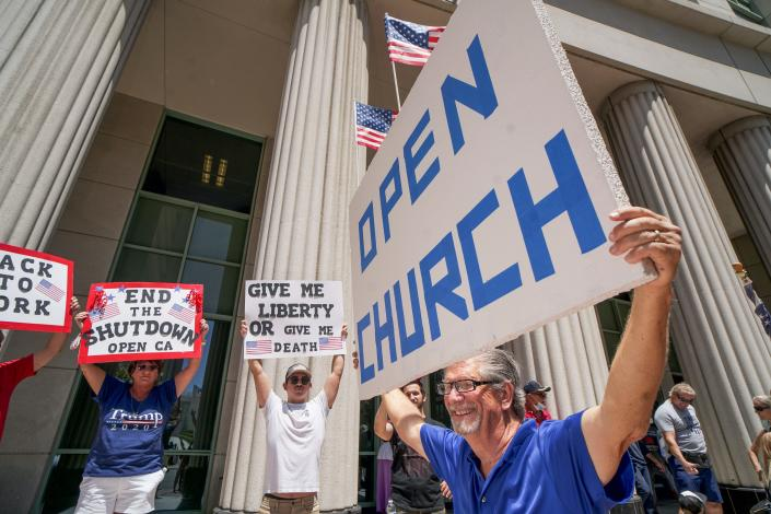 Demonstrators holding signs demanding their church to reopen, protest during a rally to re-open California and against Stay-At-Home directives on May 1, 2020 in San Diego, California. Rallies have been held at several state capitols across the country as protesters express their deep frustration with the stay-at-home orders that are meant to stem the spread of the novel coronavirus. (Sandy Huffaker / AFP via Getty Images)