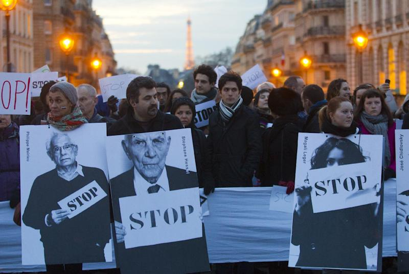 Anti-Syrian regime protesters hold placards near the Pantheon during a protest to mark the second anniversary of the uprising, in Paris, France, Friday March 15, 2013. France and Britain are pushing for the arms embargo to be scrapped in following demands by the opposition for heavy weapons to fight President Assad's forces. (AP Photo/Jacques Brinon)