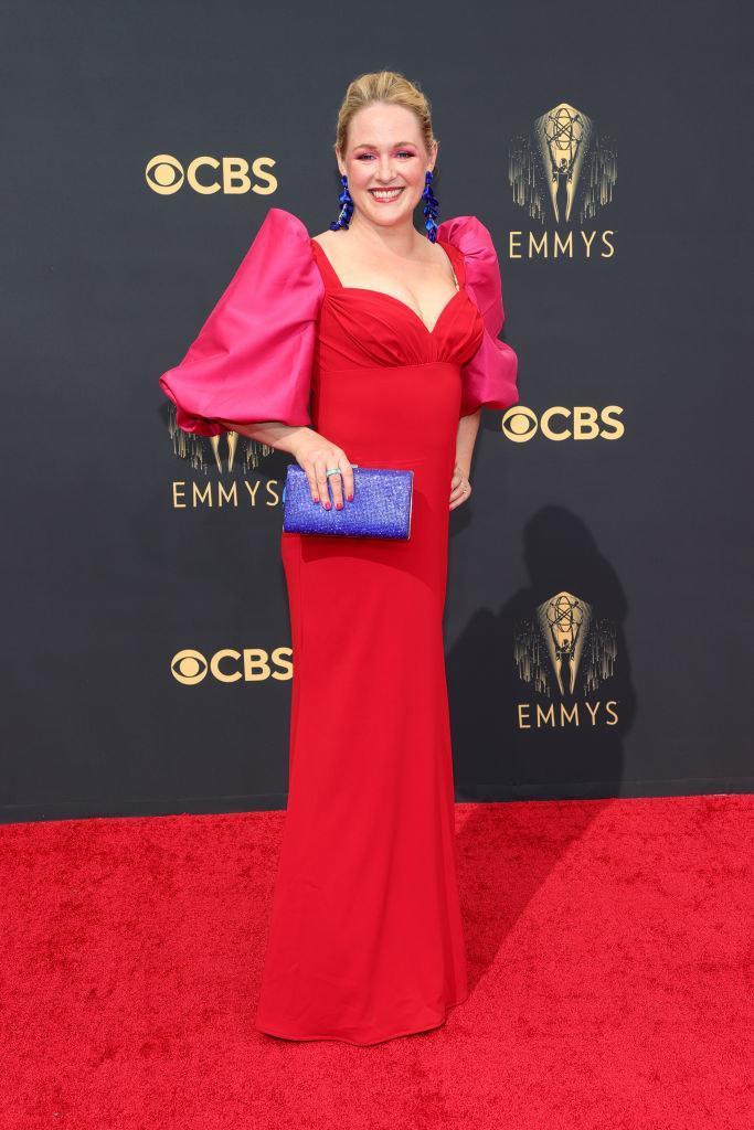 Ariel Dumas on the red carpet in a red gown with bright pink puffy sleeves