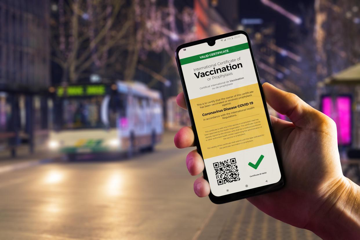 Smartphone displaying a valid digital vaccination certificate for COVID-19 in male's hand, downtown and city bus in background. Vaccination, immunity passport, health and surveillance concepts
