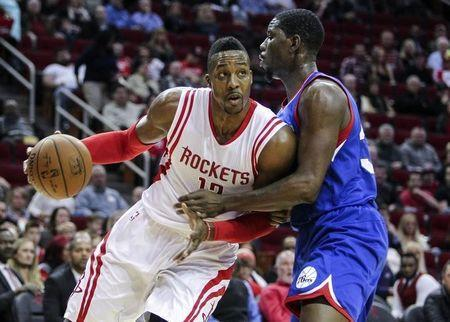 Nov 14, 2014; Houston, TX, USA; Houston Rockets center Dwight Howard (12) drives the ball as Philadelphia 76ers center Henry Sims (35) defends during the first quarter at Toyota Center. Mandatory Credit: Troy Taormina-USA TODAY Sports