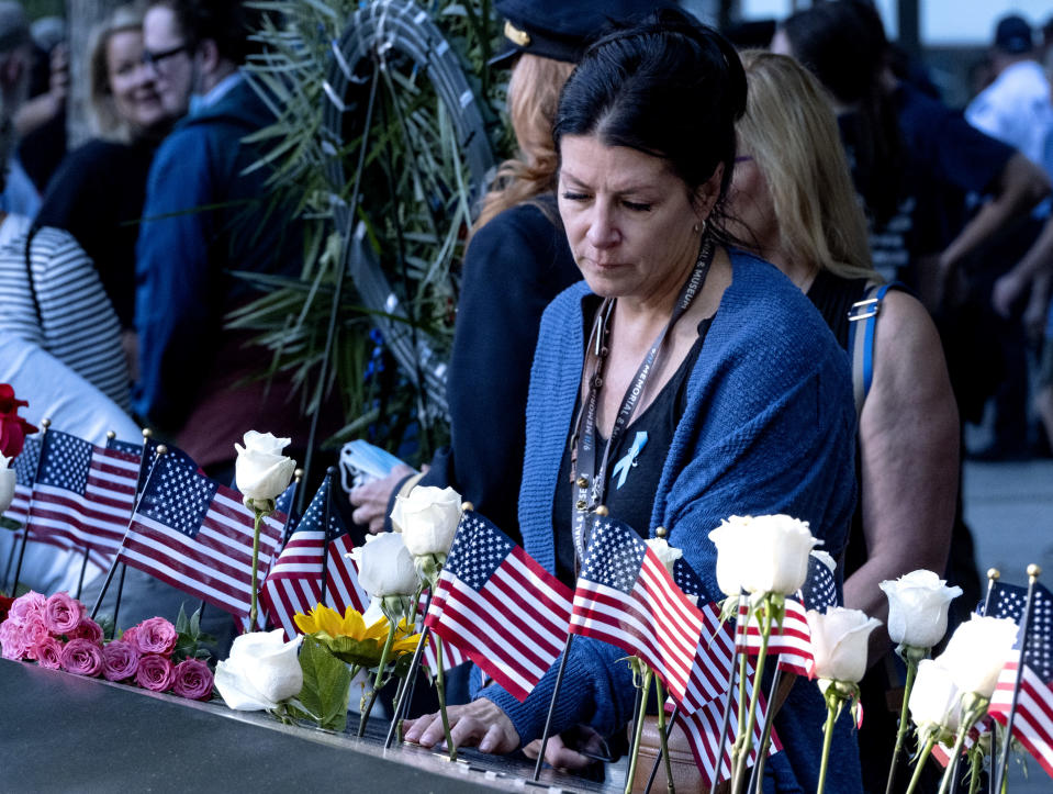 Julie Sweeney Roth, whose husband, Brian Sweeney Roth died when United Airlines flight 175 hit the World Trade Center on Sept. 11, 2001, touches his inscribed name Saturday, Sept. 11, 2021, at the National September 11 Memorial in New York on the 20th anniversary of the attacks, Saturday, Sept. 11, 2021. (Craig Ruttle/Newsday via AP, Pool)