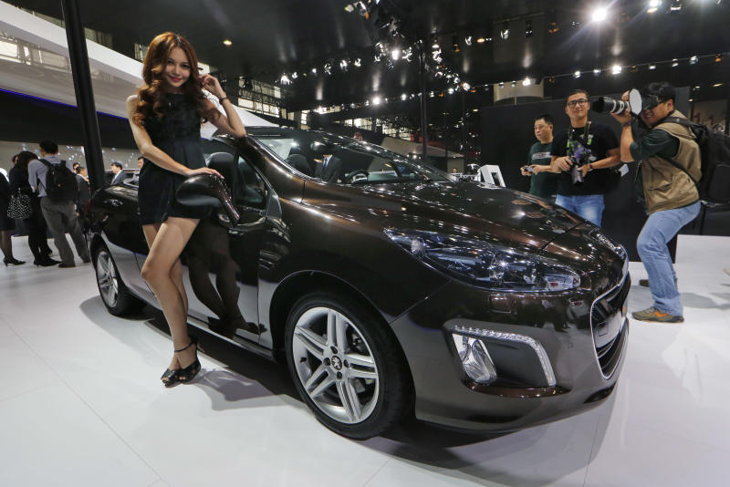 In this Nov. 21, 2013 photo, a model poses with a Peugeot 308CC at the company's booth during the Guangzhou 2013 Auto Show in China's southern city of Guangzhou. French automakers Peugeot and Renault are looking belatedly to China to revive their flagging fortunes but picked a tough time to try to expand. France's biggest auto brand, PSA Peugeot Citroen, in China since the '80s without carving out significant market share, said it will be more aggressive after its local partner, Dongfeng Motor Co., in the week of Feb. 16, 2014 agreed to take a 14 percent stake in PSA. (AP Photo/Kin Cheung)