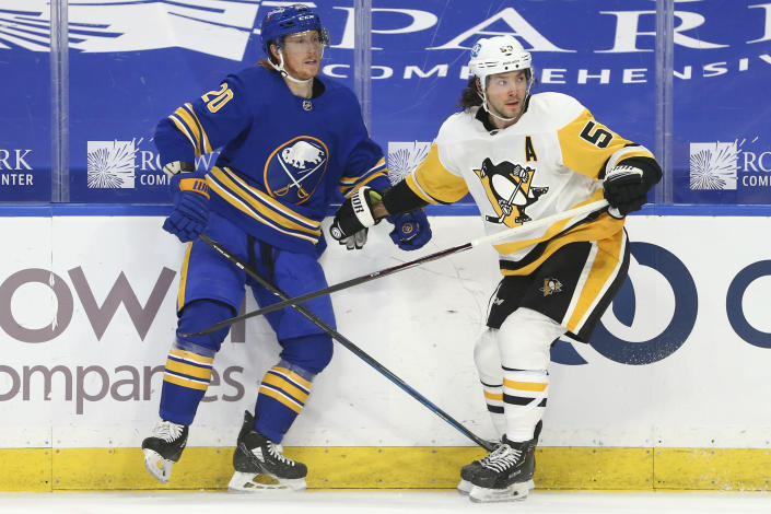 Buffalo Sabres forward Cody Eakin (20) and Pittsburgh Penguins forward Teddy Blueger (53) collide into the boards during the first period of an NHL hockey game, Sunday, April 18, 2021, in Buffalo, N.Y. (AP Photo/Jeffrey T. Barnes)