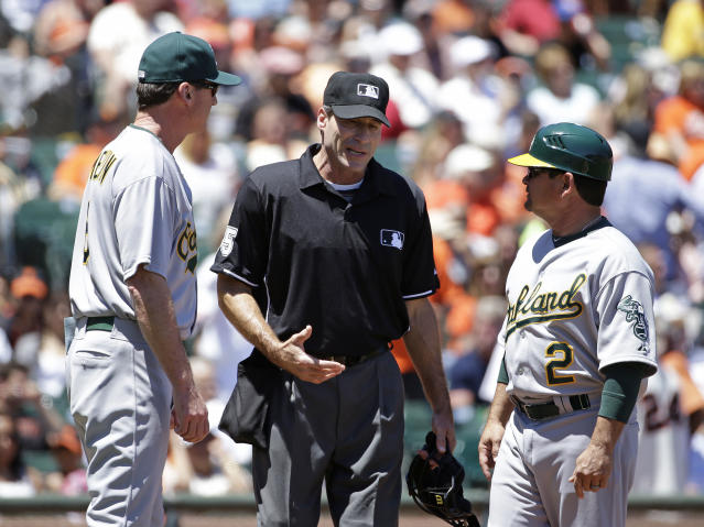 Home plate umpire Angel Hernandez, center, talks with Oakland Athletics manager Bob Melvin, left, and third base coach Mike Gallego, right, in the fourth inning of their interleague baseball game against the San Francisco Giants Thursday, July 10, 2014, in San Francisco. Hernandez replaced umpire Adrian Johnson who left the game earlier in the inning. (AP Photo/Eric Risberg)
