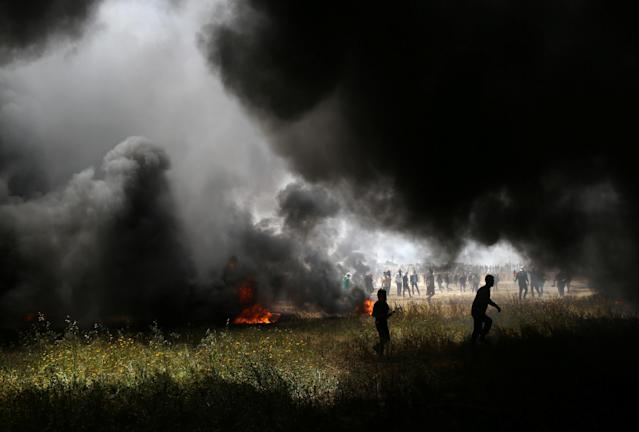 <p>Smoke rises from burning tires as Palestinian demonstrators are seen during clashes with Israeli troops at the Israel-Gaza border at a protest demanding the right to return to their homeland, in the southern Gaza Strip, April 6, 2018. (Photo: Ibraheem Abu Mustafa/Reuters) </p>