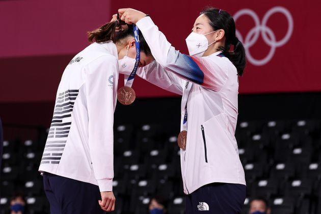 Bronze medalists Kim Soyeong, left, and Kong Heeyong of Team South Korea place their medals on each other during the ceremony for the women's doubles badminton event on Aug. 2. (Photo: Lintao Zhang via Getty Images)