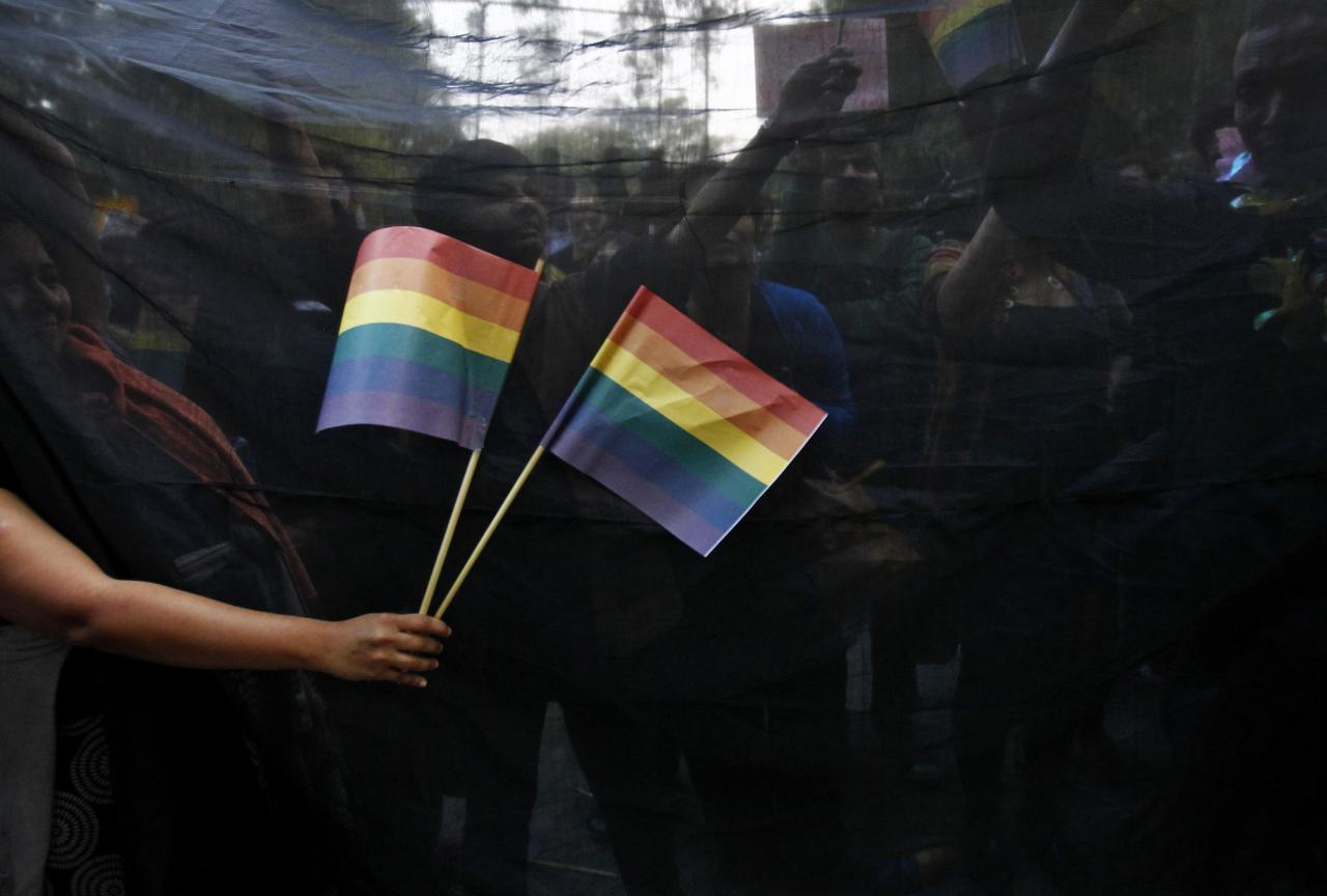 """Gay rights activists hold black cloth and wave flags as they attend a protest against a verdict by the Supreme Court in New Delhi December 11, 2013. India's Supreme Court on Wednesday reinstated a ban on gay sex in the world's largest democracy, following a four-year period of decriminalisation that had helped bring homosexuality into the open in the socially conservative country. In 2009 the Delhi High Court ruled unconstitutional a section of the penal code dating back to 1860 that prohibits """"carnal intercourse against the order of nature with any man, woman or animal"""" and lifted the ban for consenting adults. The Supreme Court threw out that decision, saying only parliament could change Section 377 of the penal code, widely interpreted to refer to homosexual sex. Violation of the law can be punished with up to 10 years in jail. REUTERS/Anindito Mukherjee (INDIA - Tags: CRIME LAW SOCIETY TPX IMAGES OF THE DAY)"""