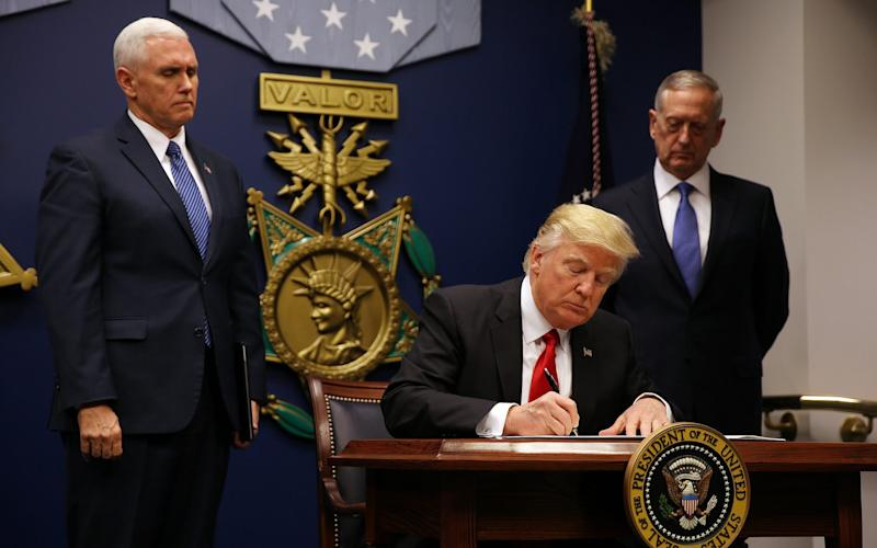 President Donald Trump signs a revised executive order for a U.S. travel ban on Monday - Credit: reuters