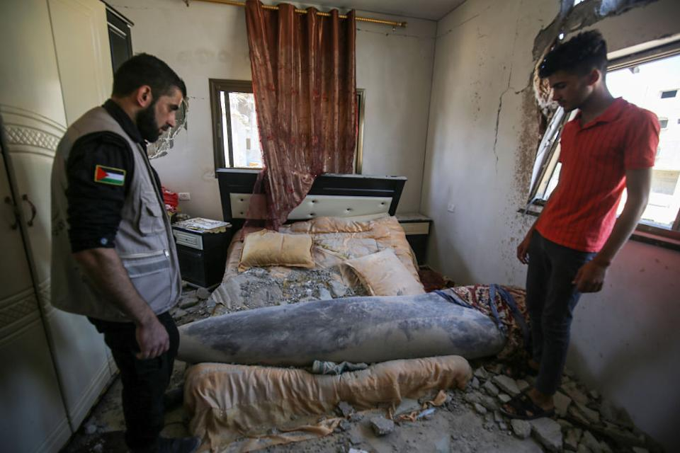 Units of the Palestinian Interior Ministry try to neutralise a missile launched by Israel that did not explode after hitting the bedroom of a house in Khan Yunis, Gaza.