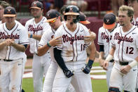 Virginia's Zack Gelof (18) celebrates his eighth inning home run with Christian Hlinka, left, Logan Michaels (12) and other teammates during an NCAA college baseball tournament super regional game against Dallas Baptist Sunday, June 13, 2021, in Columbia, S.C. Virginia won 4-0. (AP Photo/Sean Rayford)