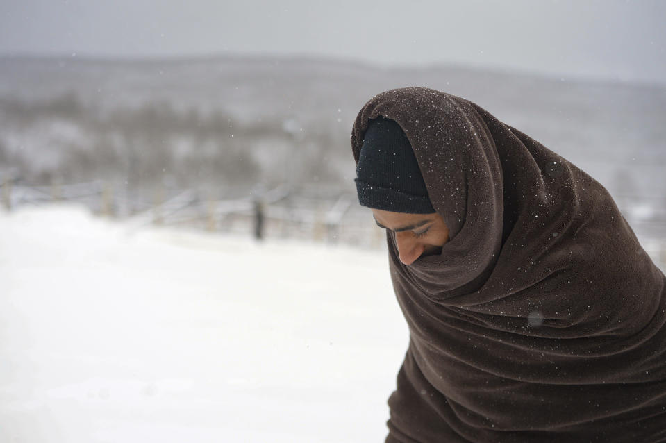 A migrant walks through the snow wrapped in a blanket at the Lipa camp northwestern Bosnia, near the border with Croatia, Saturday, Dec. 26, 2020. Hundreds of migrants are stranded in a burnt-out squalid camp in Bosnia as heavy snow fell in the country and temperatures dropped during a winter spell of bad weather after fire earlier this week destroyed much of the camp near the town of Bihac that already was harshly criticized by international officials and aid groups as inadequate for housing refugees and migrants.(AP Photo/Kemal Softic)