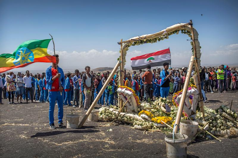 Students from Hama elementary school, who walked an hour and a half from their school in the surrounding area to pay their respects, stand next to floral tributes at the scene where the Ethiopian Airlines Boeing 737 Max 8 crashed shortly after takeoff on Sunday killing all 157 on board, near Bishoftu, south-east of Addis Ababa, in Ethiopia Friday, March 15, 2019. Analysis of the flight recorders has begun in France, the airline said Friday, while in Ethiopia officials started taking DNA samples from victims' family members to assist in identifying remains. (AP Photo/Mulugeta Ayene) ORG XMIT: NAI112
