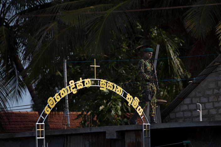 An officer of Special Task Force stands guard atop a building as funerals for Easter Sunday bomb blast victims take place at the Methodist burial ground in Negombo, Sri Lanka, April 23, 2019. (Photo: Gemunu Amarasinghe/AP)