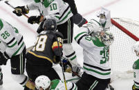 Dallas Stars goalie Ben Bishop (30) is hit by Vegas Golden Knights' William Carrier (28) during the third period of an NHL hockey playoff game Monday, Aug. 3, 2020, in Edmonton, Alberta. (Jason Franson/The Canadian Press via AP)