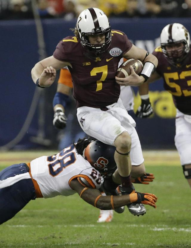Minnesota quarterback Mitch Leidner (7) rushes for a gain as Syracuse's Jeremi Wilkes (28) reaches to tackle him during the second quarter of the Texas Bowl NCAA college football game on Friday, Dec. 27, 2013, in Houston. (AP Photo/David J. Phillip)