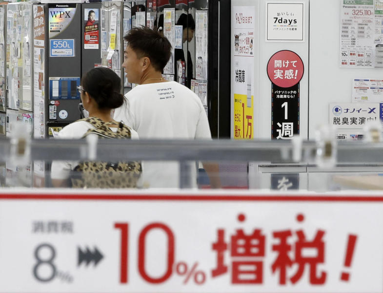 """FILE - In this Sept. 30, 2019, file photo, a signboard says """"Consumption tax hike, 8 percent to 10 percent"""", at a mass home electronics retailer in Tokyo. Japan reports on Thursday, Nov. 14, 2019 its economy grew at an annual pace of 0.2% in July-September, supported by consumer purchases ahead of a tax hike. (Shinji Kita/Kyodo News via AP, File)"""