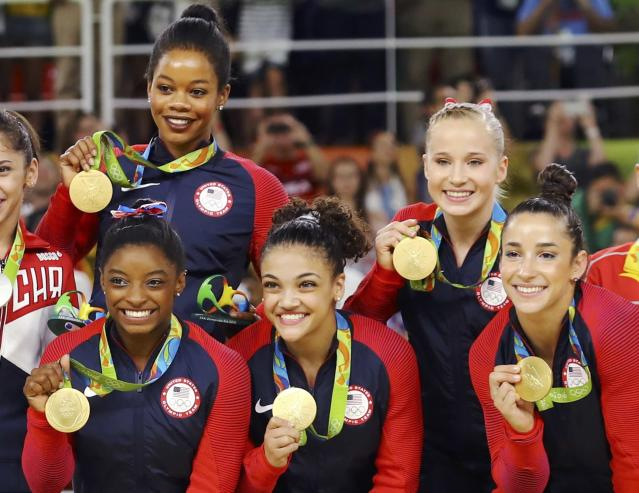 2016 Rio Olympics - Artistic Gymnastics - Final - Women's Team Final - Rio Olympic Arena - Rio de Janeiro, Brazil - 09/08/2016. Simone Biles (USA) of USA, Gabrielle Douglas (USA) of USA (Gabby Douglas), Laurie Hernandez (USA) of USA, Madison Kocian (USA) of USA, Alexandra Raisman (USA) of USA (Aly Raisman) pose with their gold medals on the podium after winning the women's team final. REUTERS/Mike Blake FOR EDITORIAL USE ONLY. NOT FOR SALE FOR MARKETING OR ADVERTISING CAMPAIGNS.