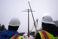 Workers watch the installation of the first pole of Central Maine Power's controversial hydropower transmission corridor, Tuesday, Feb. 9, 2021, near The Forks, Maine. The pole was erected on an existing corridor that had been widened near Moxie Pond. (AP Photo/Robert F. Bukaty)