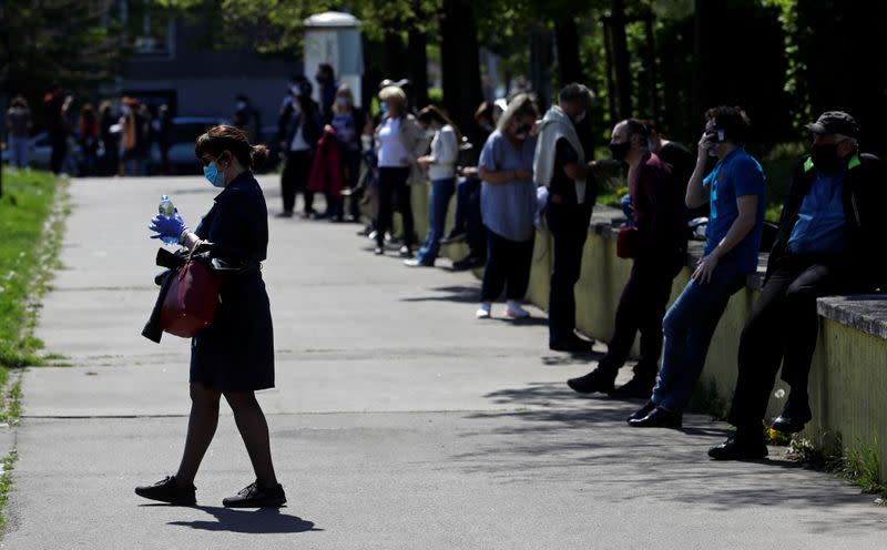 People keep social distance while waiting in line in Prgaue