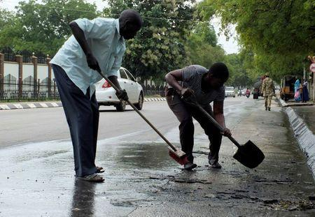 South Sudan civilians clean the streets of dried blood from an unidentified soldier who was killed following the recent fighting outside the Presidential State House in South Sudan's capital Juba, July 14, 2016. REUTERS/Stringer