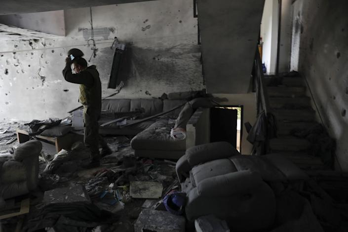 A soldier walks through the wreckage of a living room.