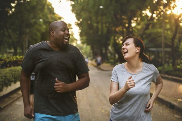 A man and a woman going for a run and smiling